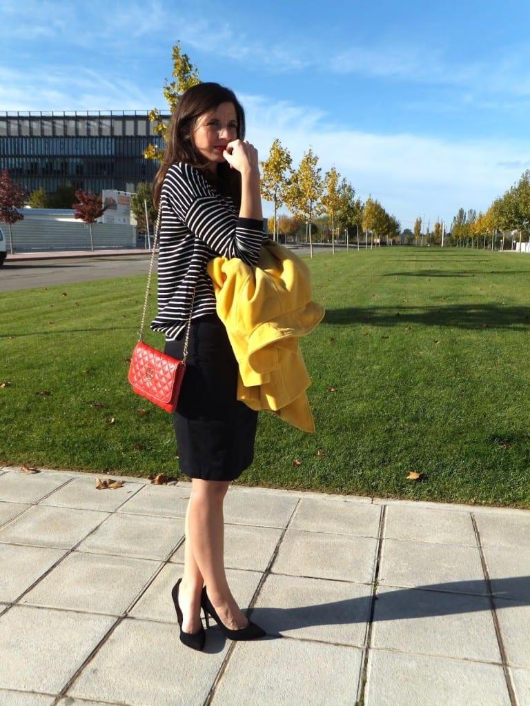 look con bolso rojo con abrigo amarillo y falda negra