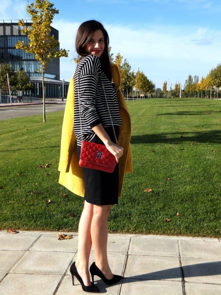 combinar abrigo amarillo con falda negra y jersey a rayas