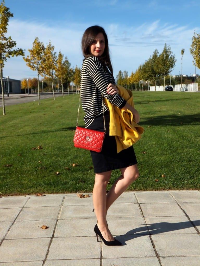 chica con abrigo amarillo con falda negra y jersey a rayas